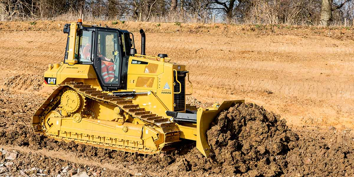 A yellow excavator moving soil
