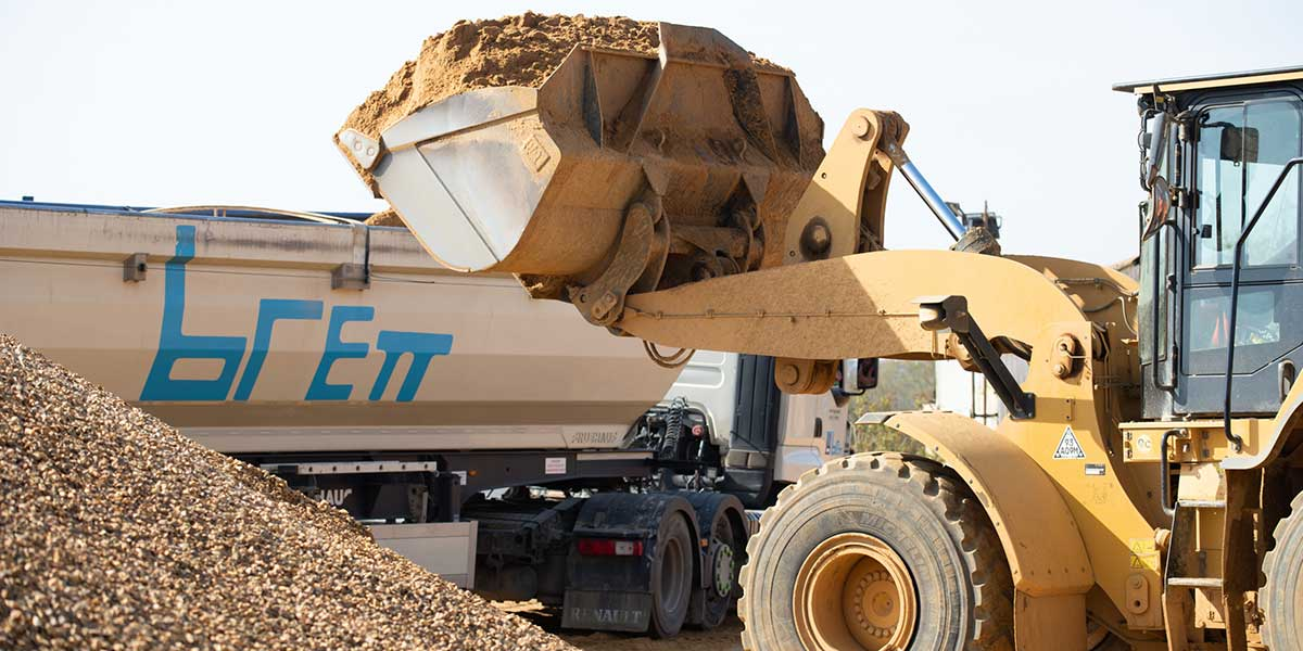 A digger putting aggregates into a Brett lorry for distribution
