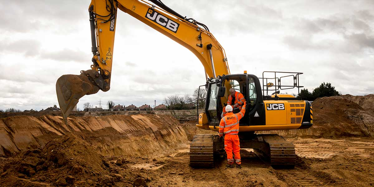 A JCB digger excavating material from a site