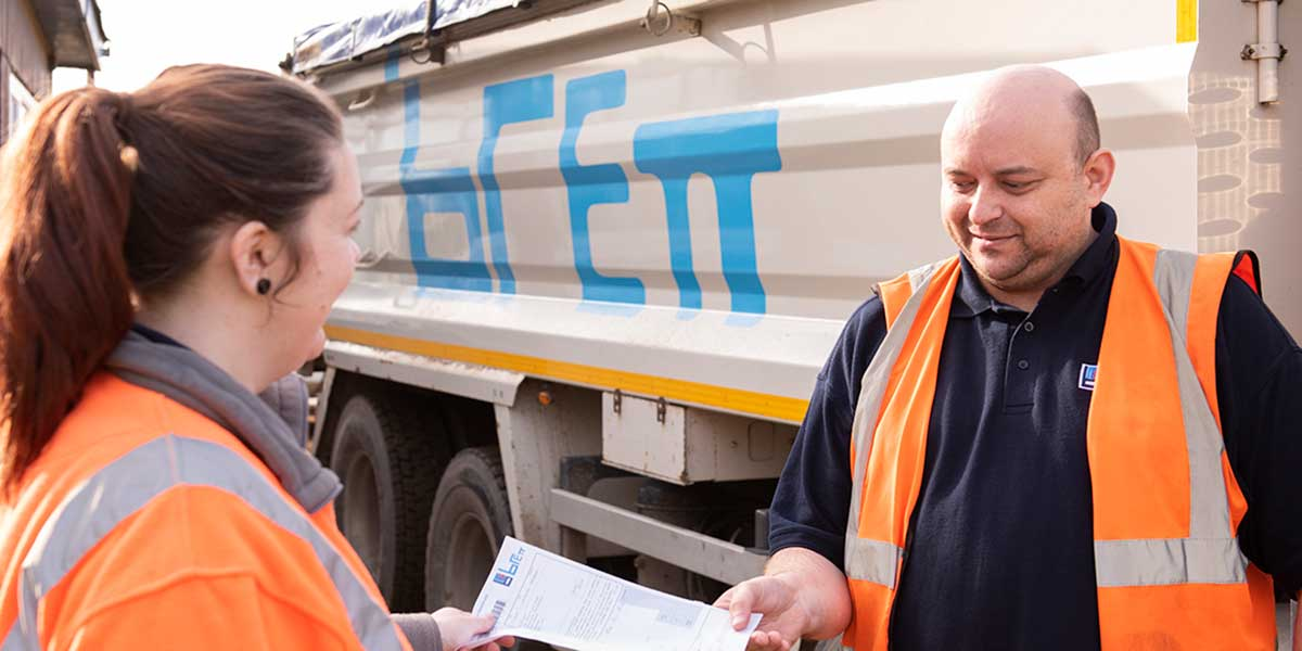 A person recieving paperwork from a Brett lorry driver